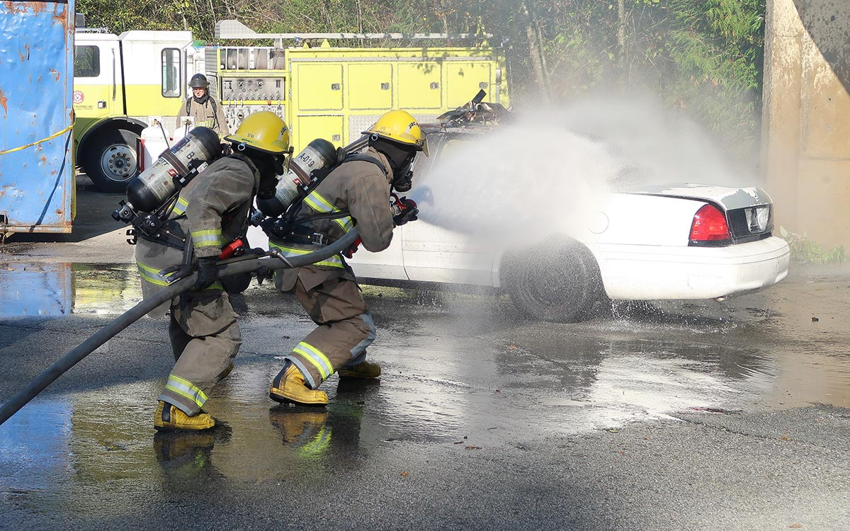 Britt Benn, left, helps demonstrate how to extinguish a car fire as part of celebration activities recognizing the completion of seven weeks of hands-on training at JIBC's Maple Ridge campus.