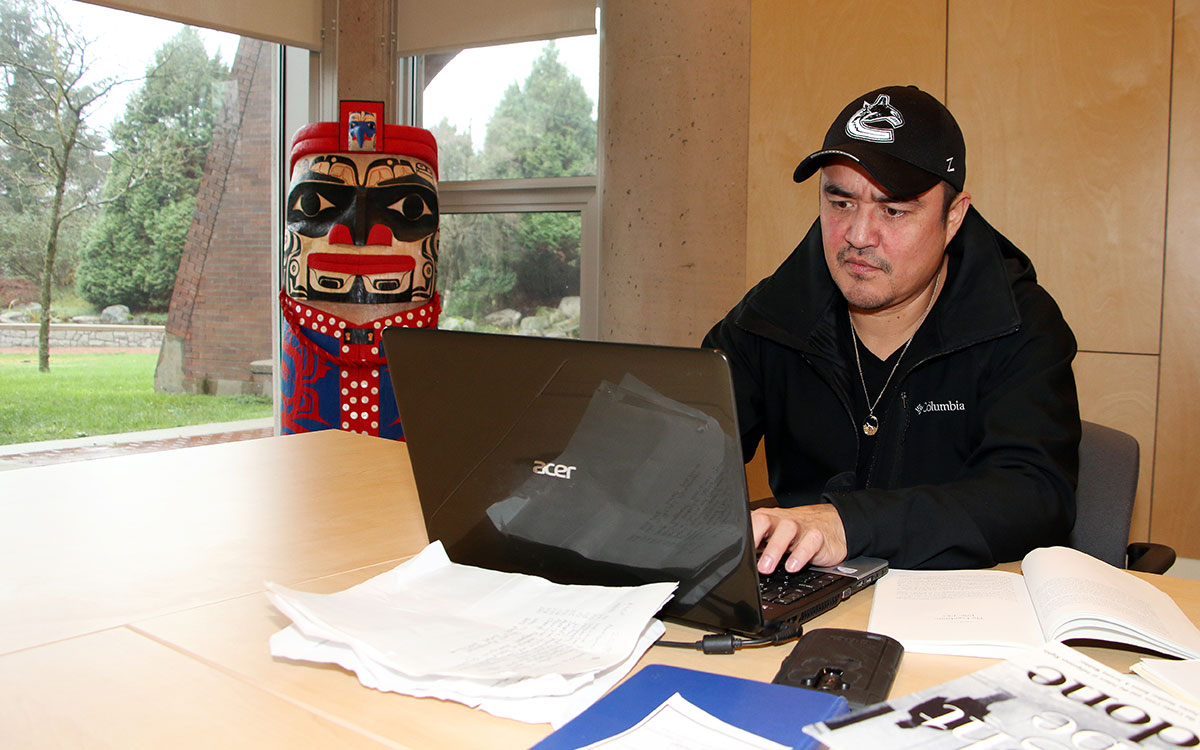 Malcolm Stewart, of the Nisga'a Nation, is a student in the Justice and Public Safety Certificate program at JIBC. Here he works on an essay in JIBC's Aboriginal Gathering Place as a house post by Nisga'a artist Mike Dangeli looks on.