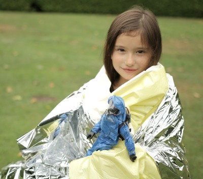 Child wrapped in rescue blanket participating in decontamination drill
