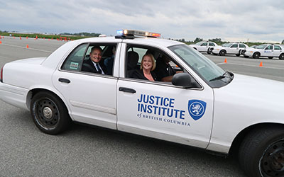 MLAs Lisa Beare and Bob D'Eith, and Michel Tarko about to experience demonstration of first responder driving skills.